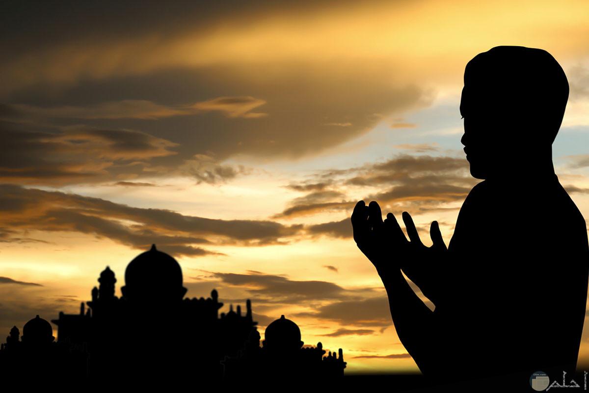 خلفية دينية ابيض و اسود دينية لشاب يدعي الله عز وجل و في الخلفية مسجد.
