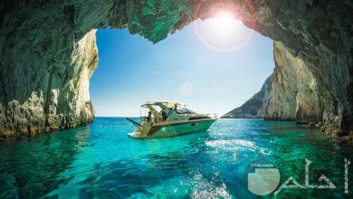 مركب في البحر مع مياه صافية و كهف صخري - منظر خلاب بحري.