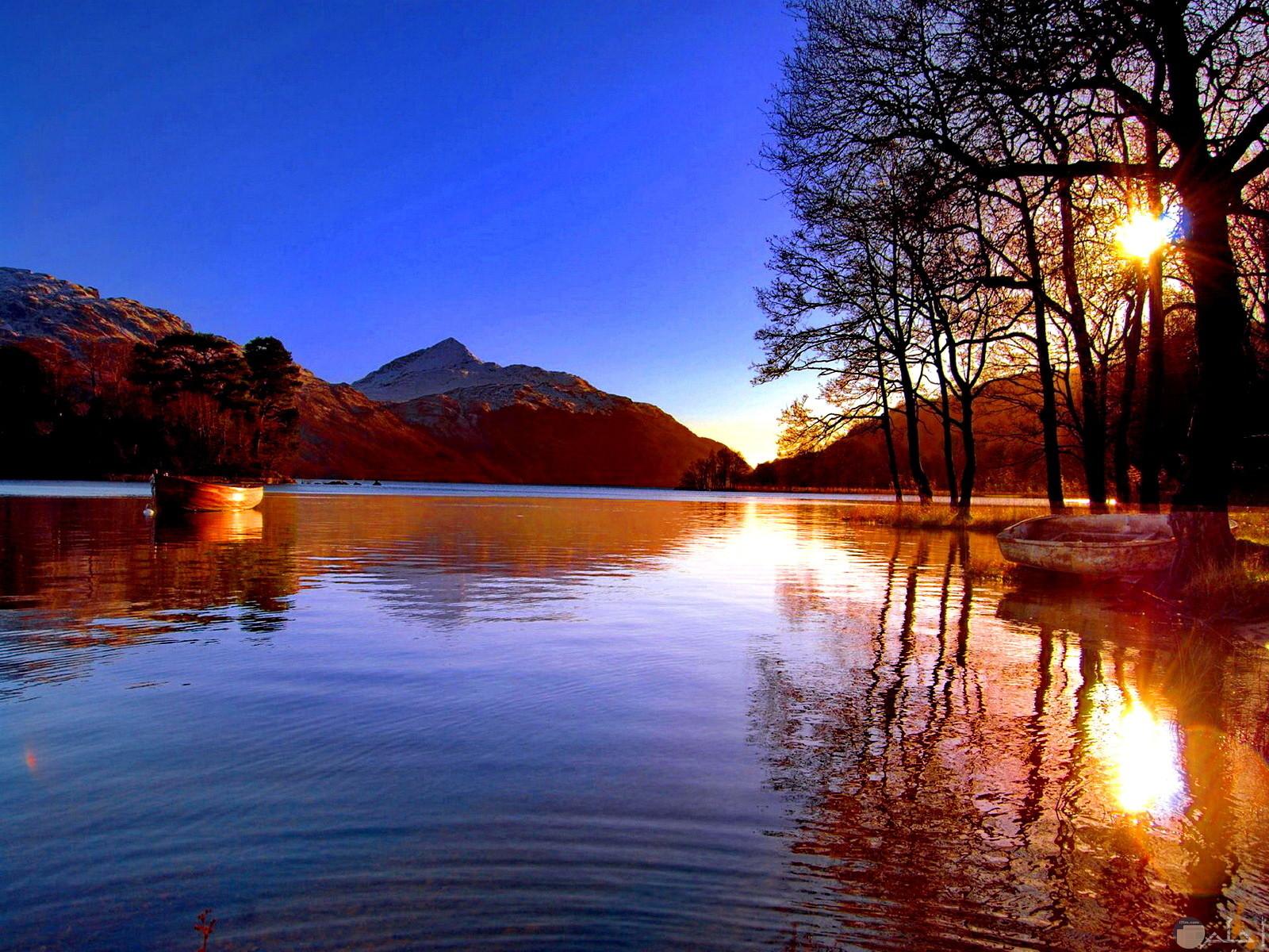 جمال الشمس خلف الجبال في وجود الجبال و الأشجار.