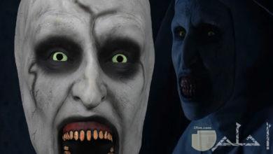 قناع أو وجه مخيف مرعب بفم مفتوح و أسنان بارزة و عين يحيط بها السواد و هالة سوداء حول العين.