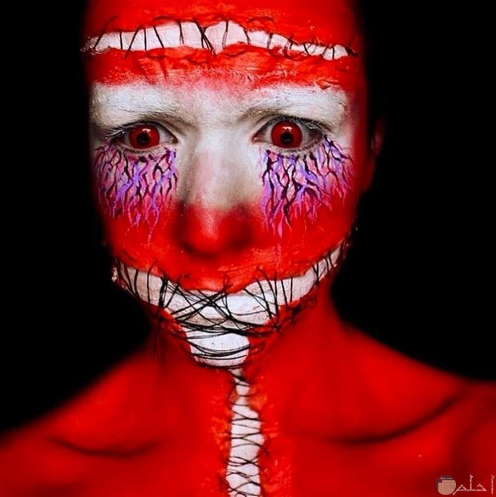 وجه مخيف و مرعب يظهر الخيوط التى تغلق فمه و عقله و كأنها ترمز أو تعبر عن الحبس و عم وجود حرية.