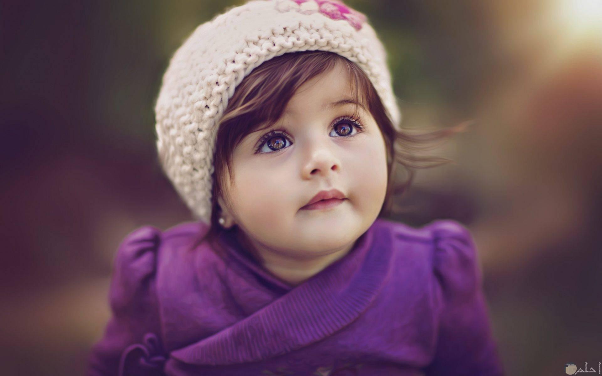طفلة جميلة ترتدى فستان موف وكاب بيج