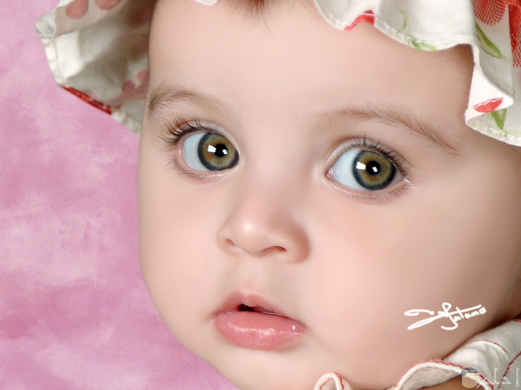 صورة بنت صغيورة عيونها ملونه تنظر على شئ