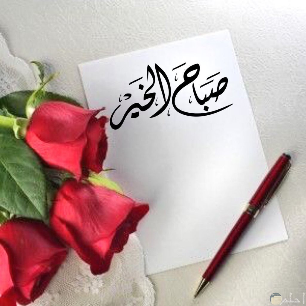 صباح الخير مكتوبة على ورقة بجوار زهور حمراء.