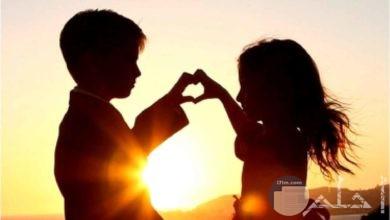 طفلين ولد و بنت يصنعان بأيديهما قلب.