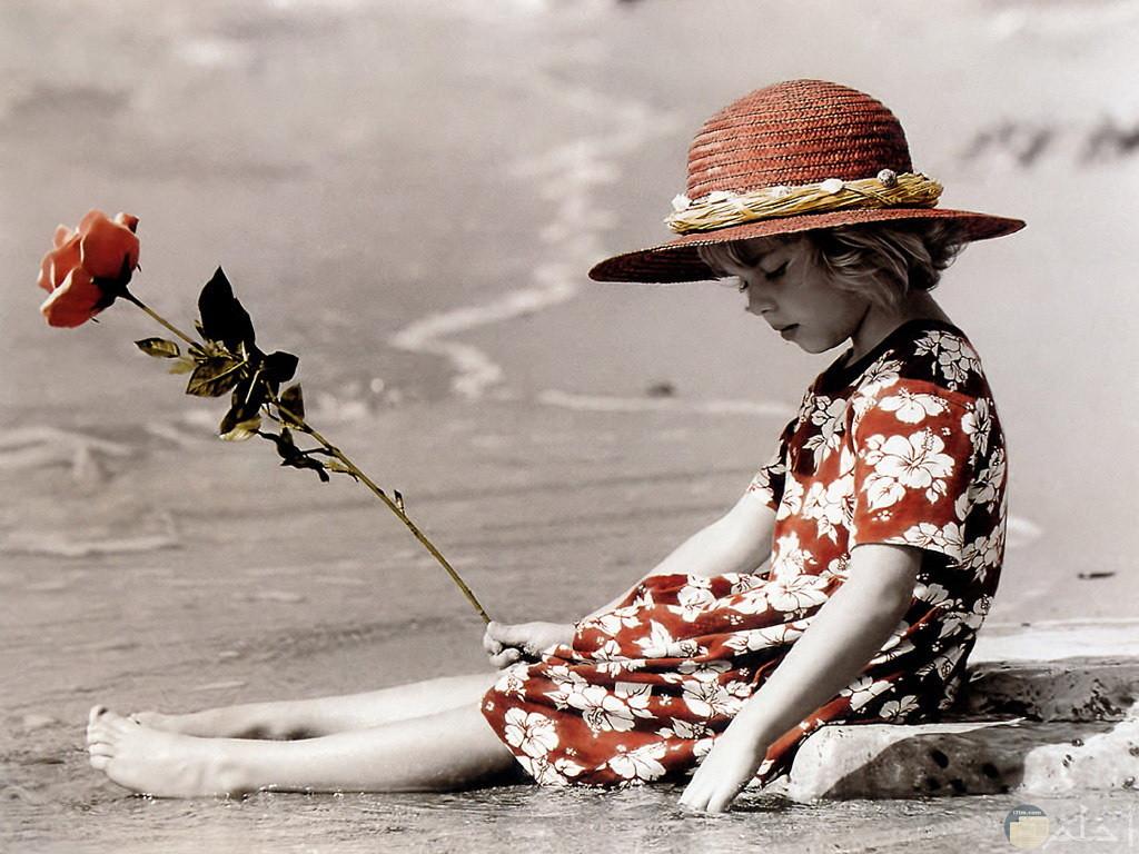 بنت صغيرة تجلس على الشاطئ .