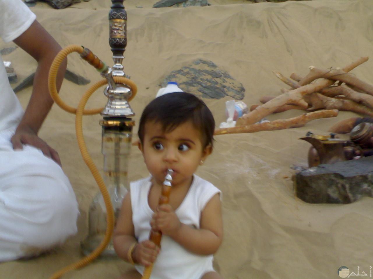 ولد صغير يشرب شيشة بجوار والده.