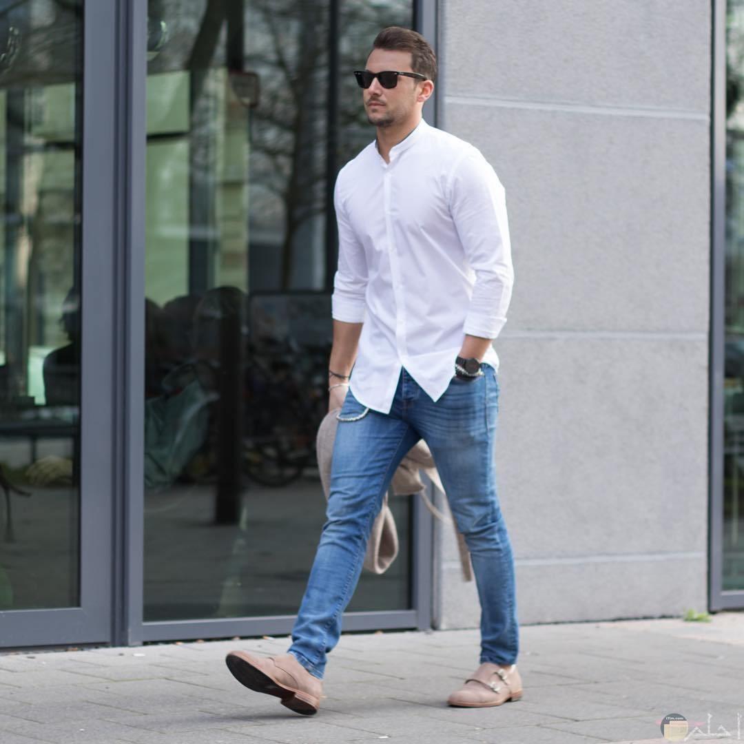 رجل يرتدى قميص ابيض وبنطلون جينز وشوز