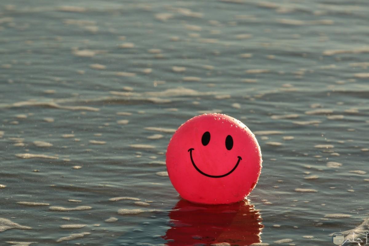 كرة حمراء تطفو على مياة البحر و مرسوم عليها وجه مبتسم.