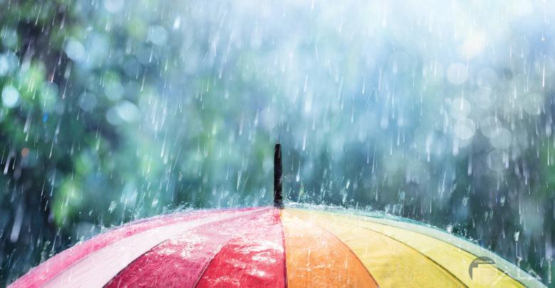 منظر سقوط المطر فوق مظلة ملونة.