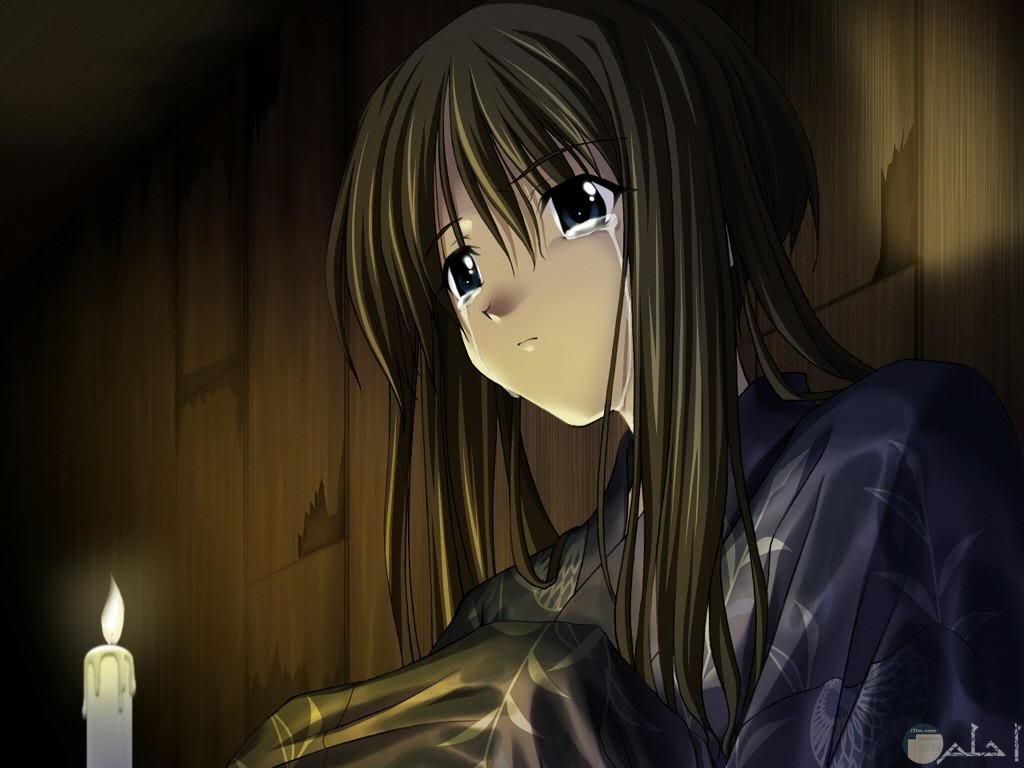 رسمة فتاة أنمي حزينة تجلس أمام شمعة مضيئة.
