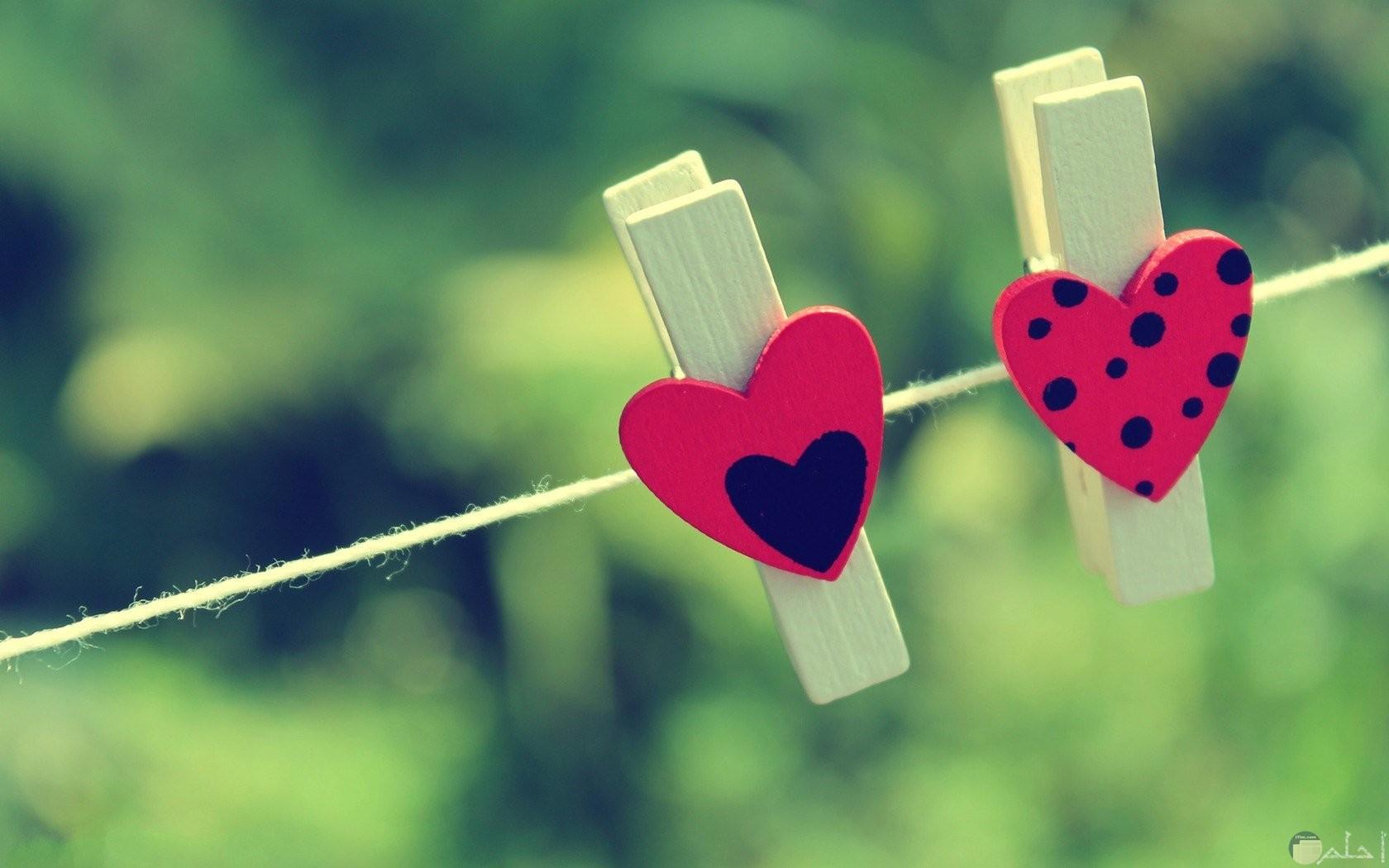 مشبك به قلب احمر منقط بالاسود ومشبكك اخر بها قلب احمر وقلب اسود صغير