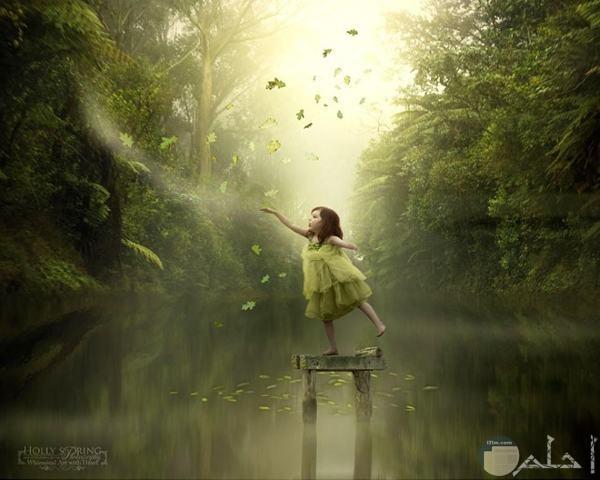 فتاة صغيرة تمسك بورق الشجر
