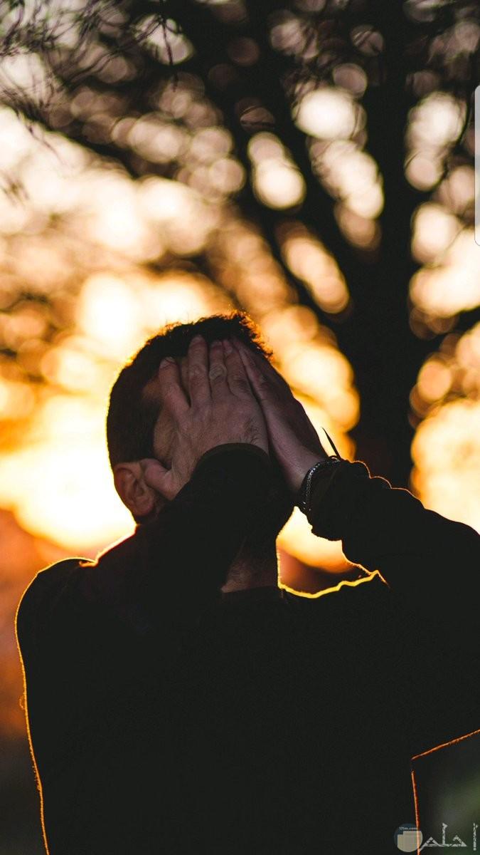 شاب يضع يديه على وجهه و قت غروب الشمس.