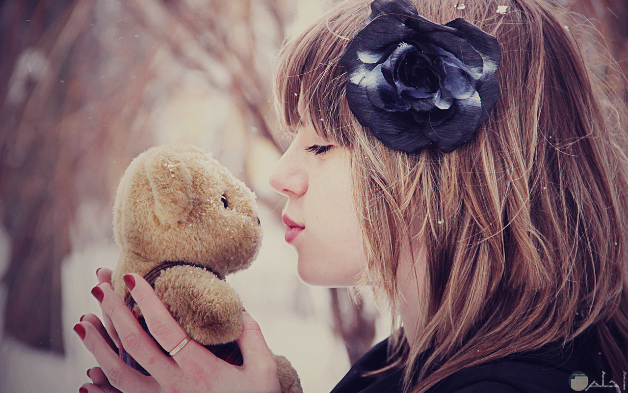 فتاه صغيرة تحمل دبدوب وتقبلها