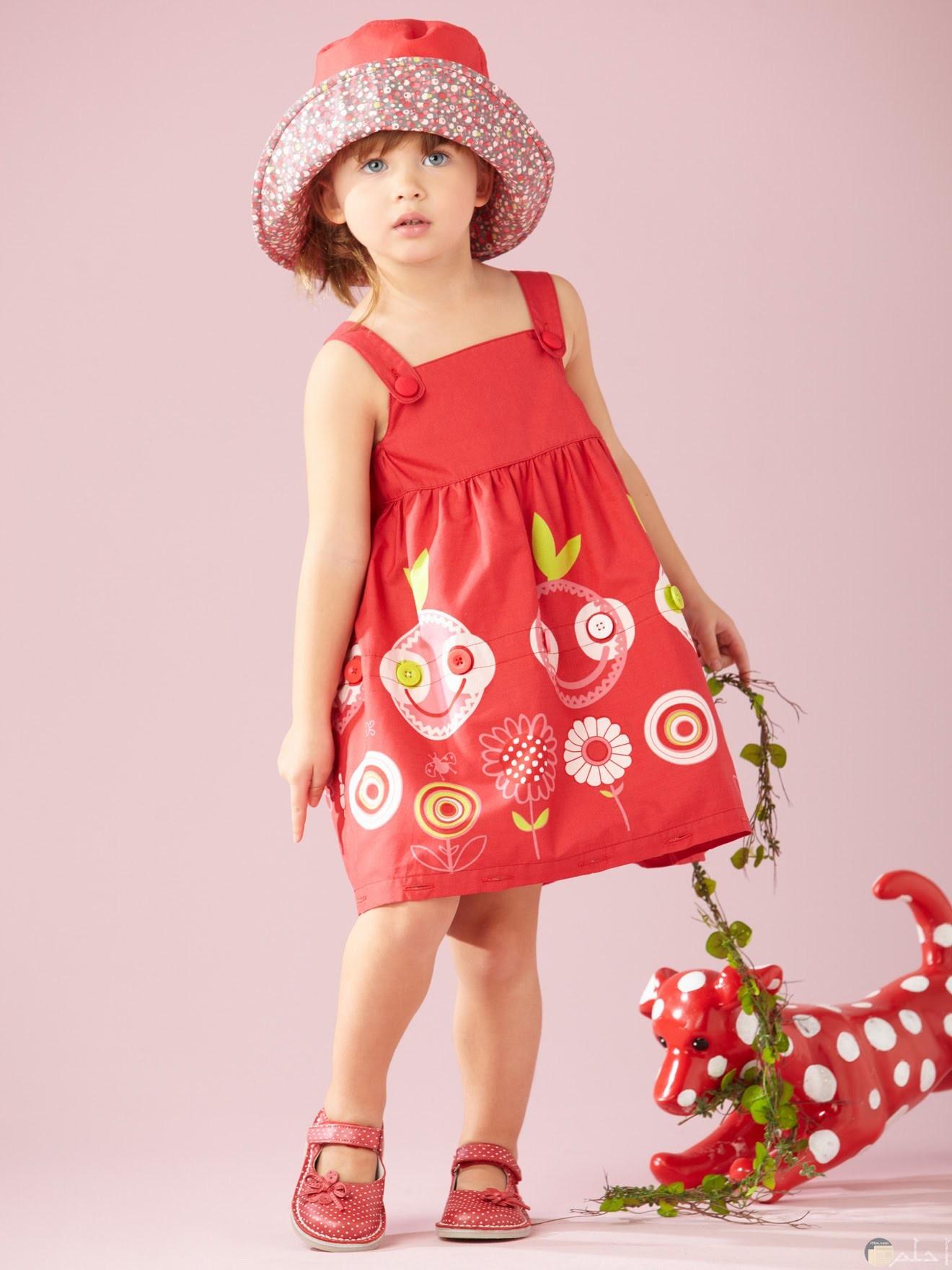 بنوته ترتدى فستان احمر وقبعه