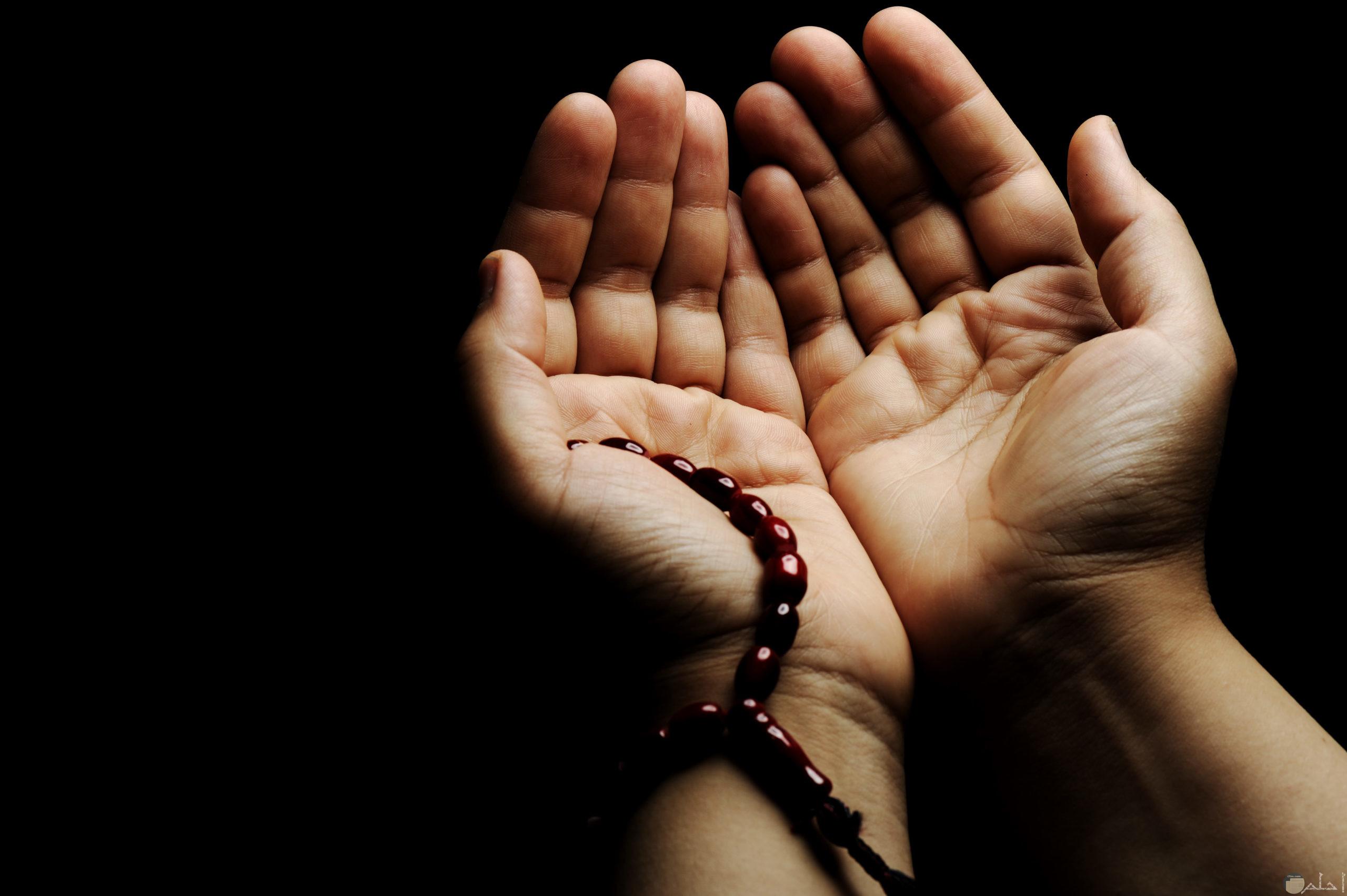 يد تمسك سبحة و تترفع بالدعاء للسماء.