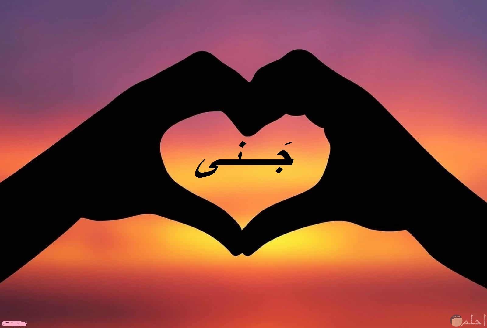 اسم جنى داخل قلب من الاصابع مع غروب الشمس.