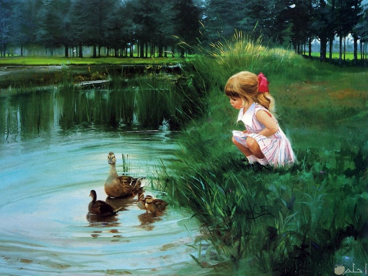 فتاه جالسة امام مجري ماء بها بط