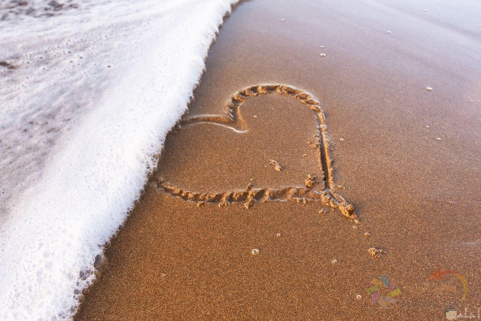 قلب مرسوم على الرمل امام شاطئ بحر