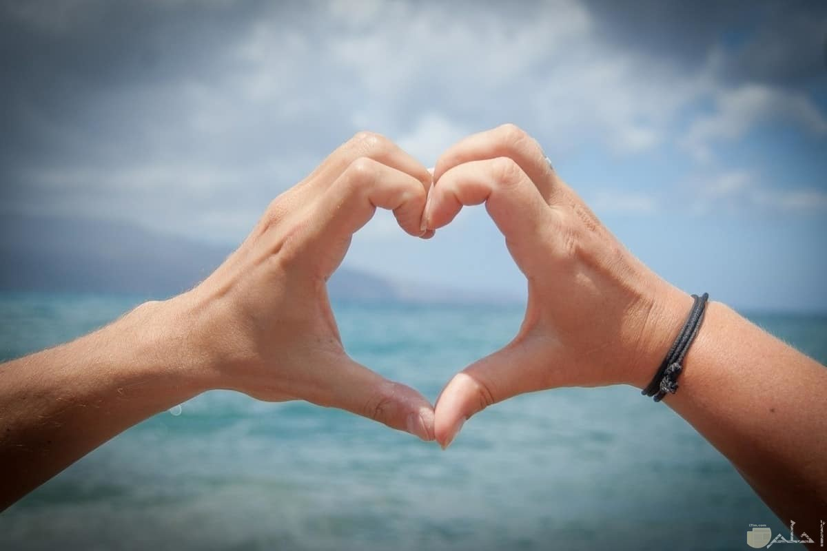 ولد و فتاة يصنعان قلب بأصابعهما.