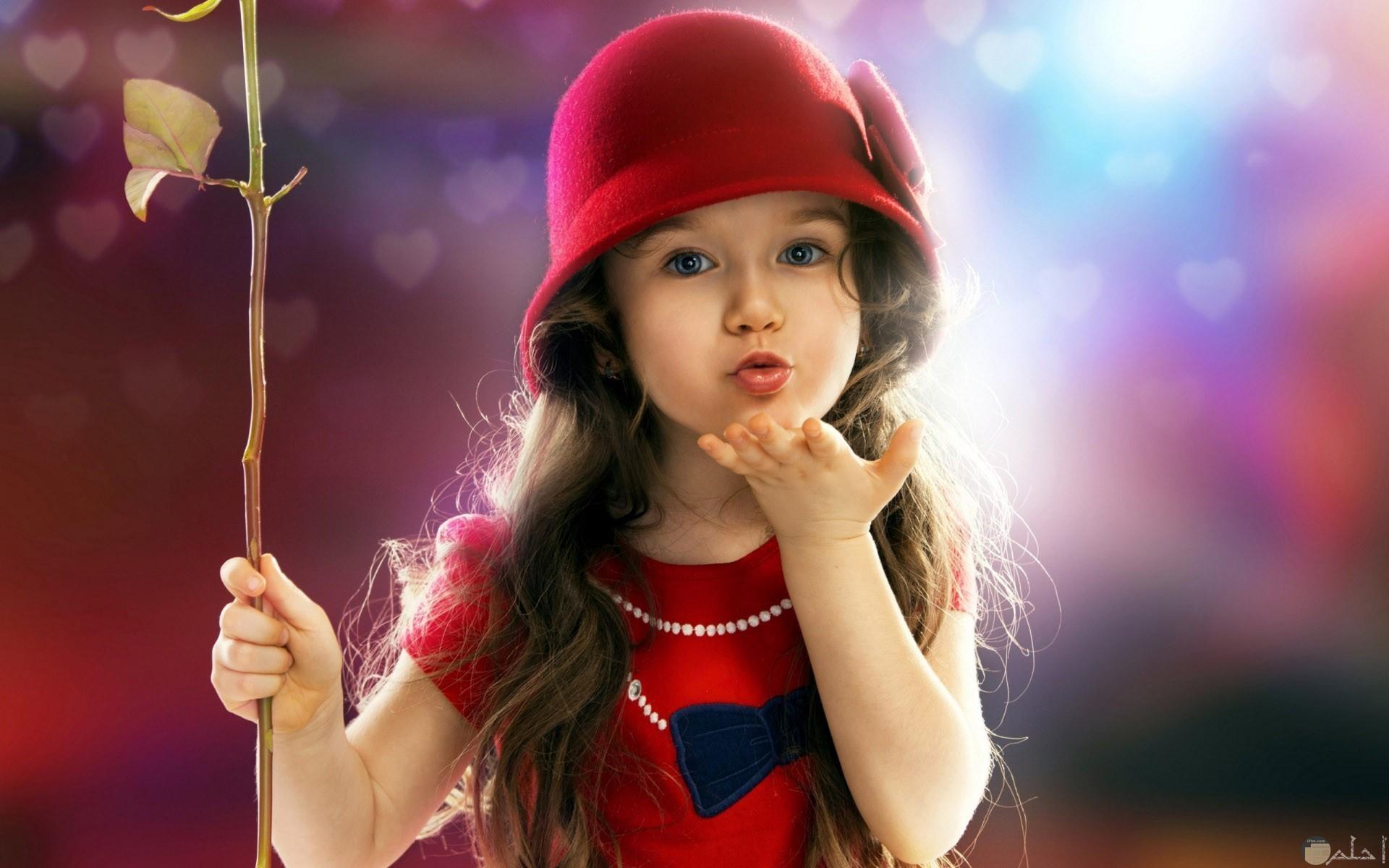 بنت جميلة بفستان و طقية حمراء تعطي قبلة.