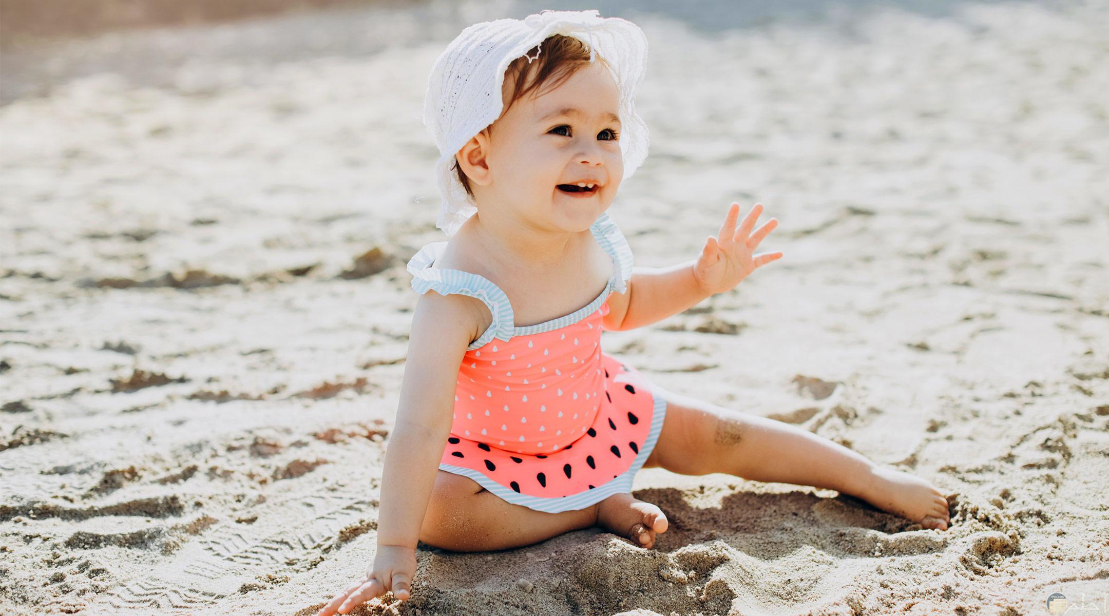 طفلة صغيرة على رمال الشاطئ.