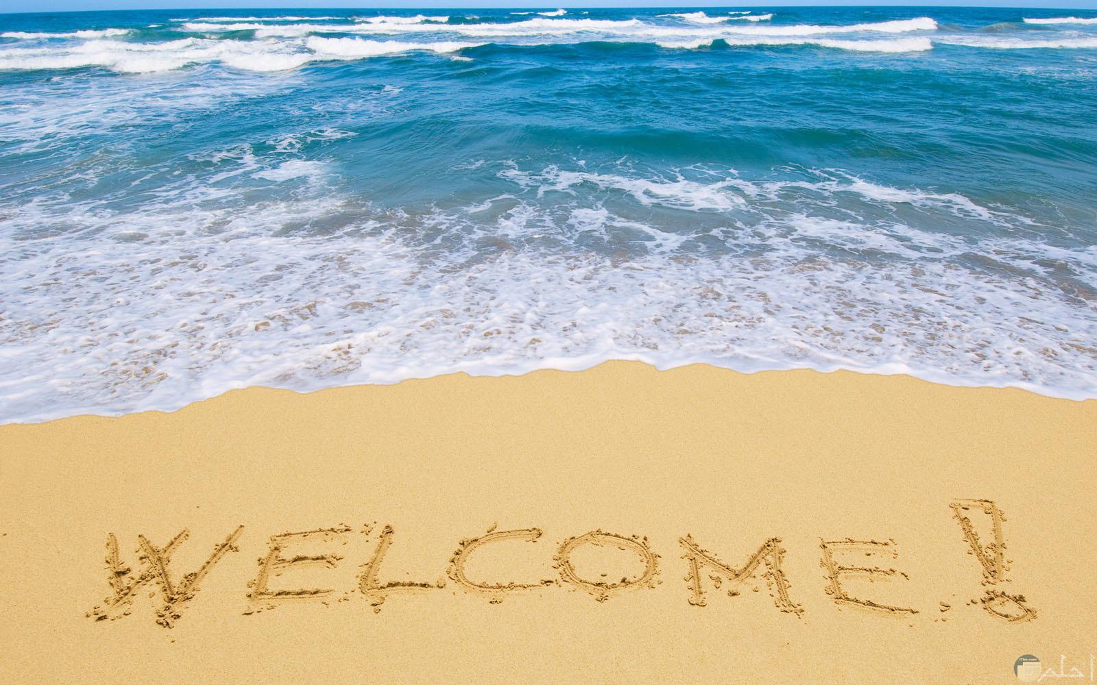 شاطئ بحر ورمال مكتوب عليها مرحبا