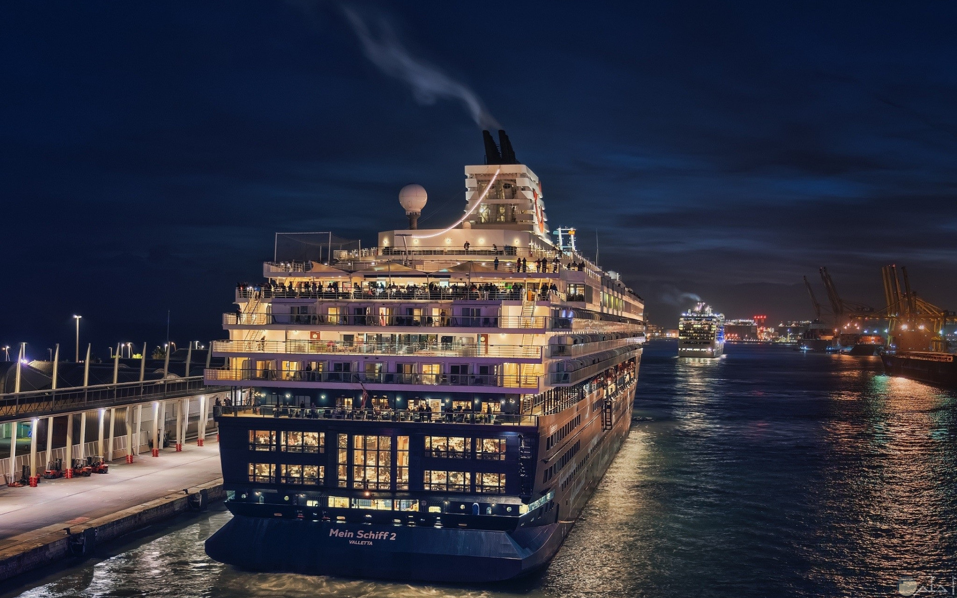 صورة سفينة وسط المياة ليلاً و أنوارها.