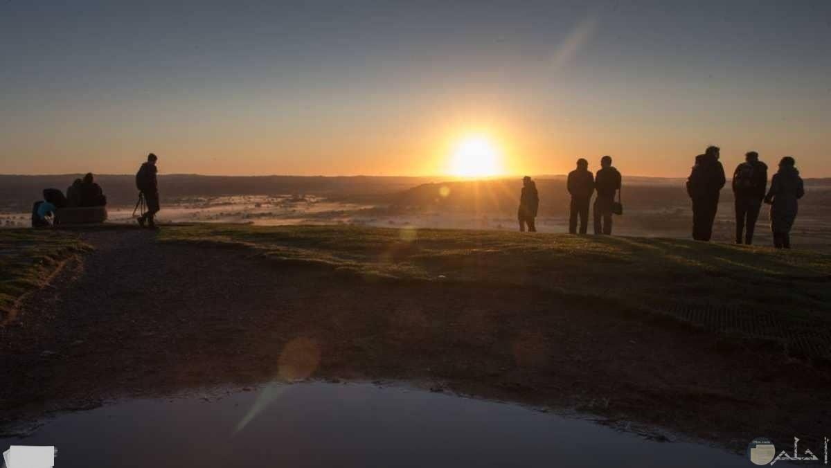 صورة لشروق الشمس و البعض يتابعها.