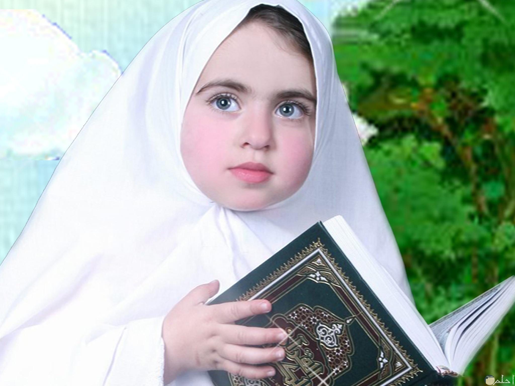 صورة لبنت صغيرة محجبة تمسك المصحف.