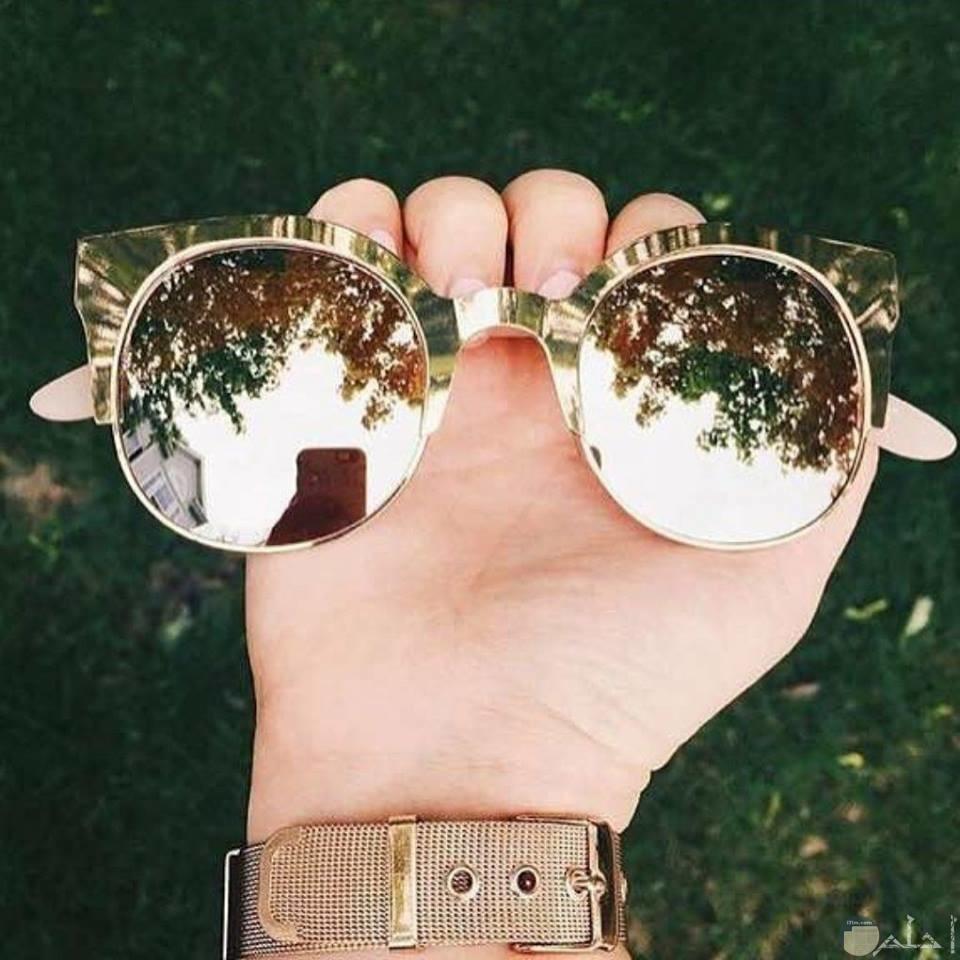 صورة لنظارة بيد فتاة.