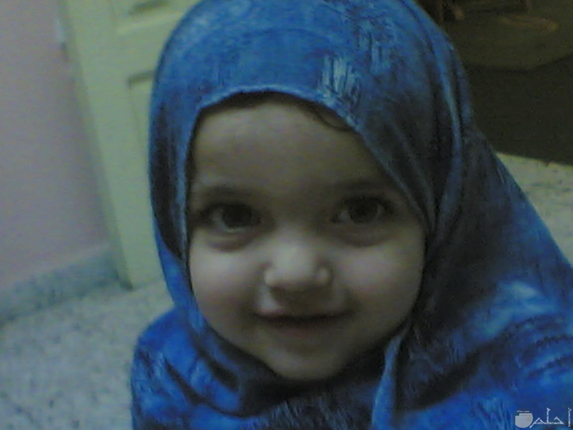 صورة بنت صغيرة بالحجاب تضحك.