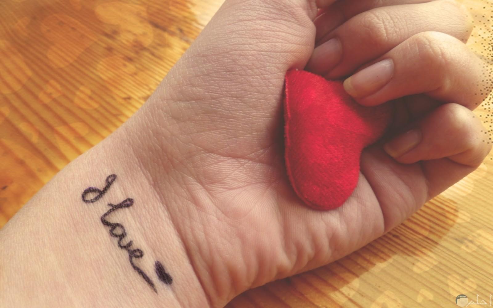 يد بها قلب احمر