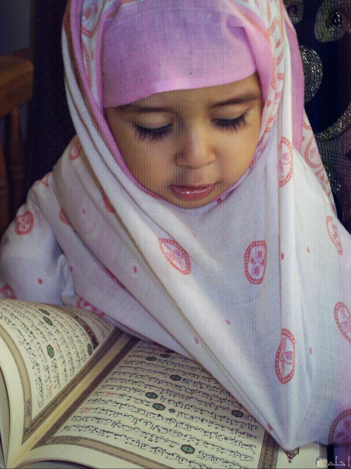 صورة بنت صغيرة محجبة مع كتاب الله خاشعة.