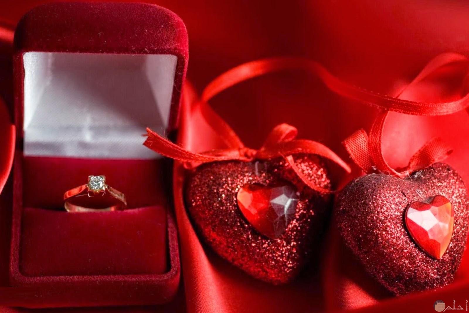 قلبين لونهم احمر بجوار علبه بها خاتم