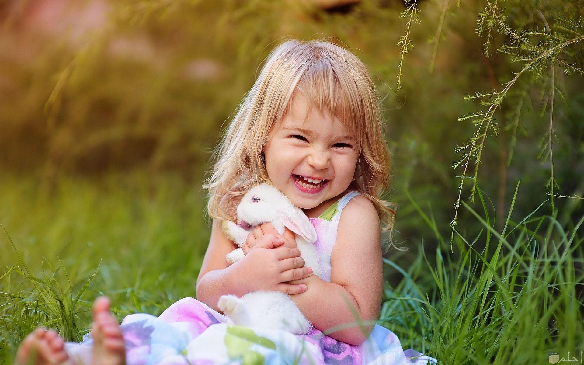 صورة جميلة لبنت تداعب أرنب.