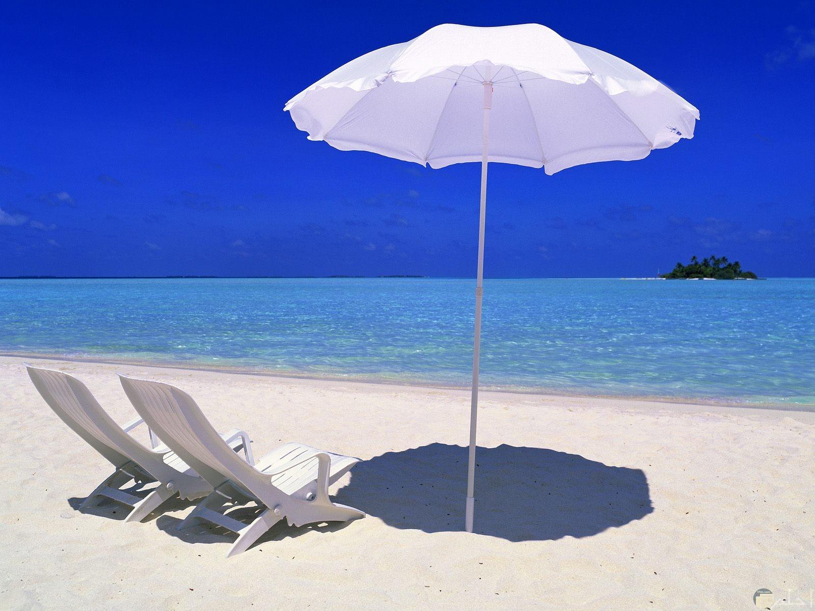 شمسية وكرسيين على البحر