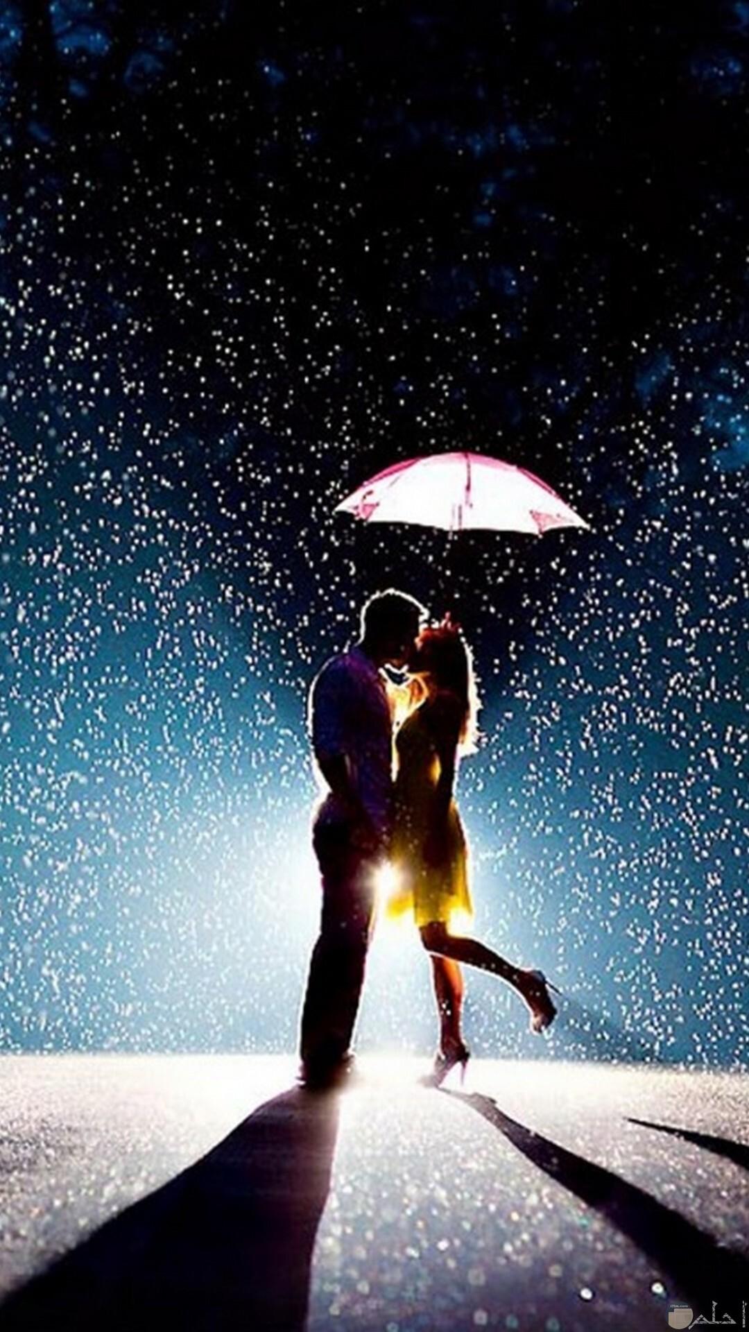 ثنائي جميل من العشاق تحت المطر.