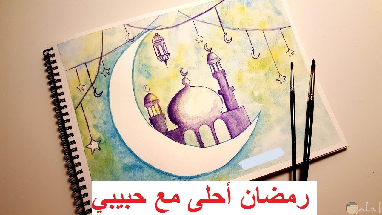 رسمة مسجد و هلال رمضان و الزينة مكتوب عليها رمضان أحلى مع حبيبي.
