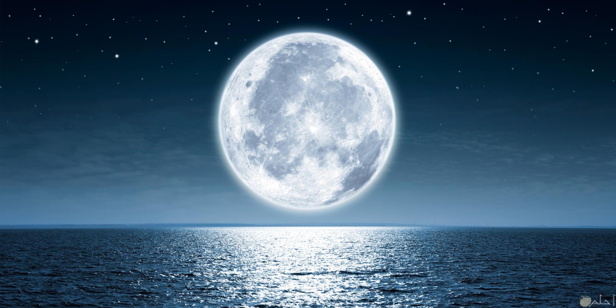 القمر و هو يعلو سطح البحر فى صورة.