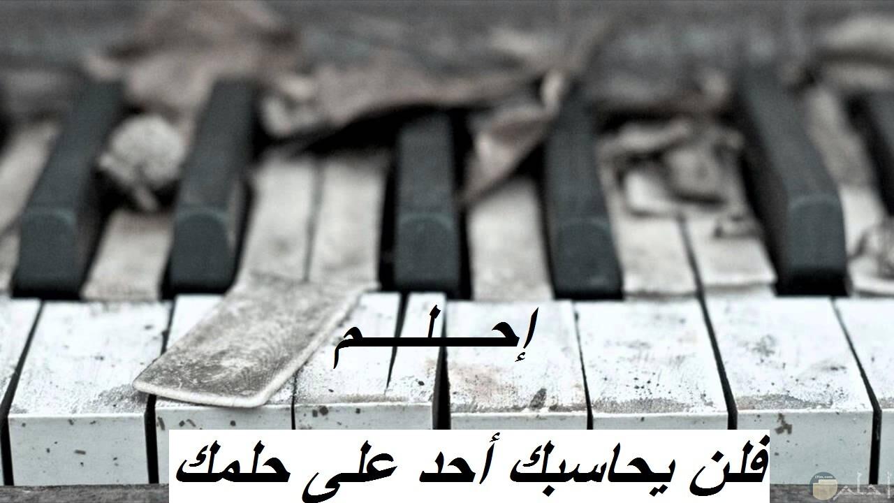 صورة بيانو أبيض و أسود مكتوب عليه.