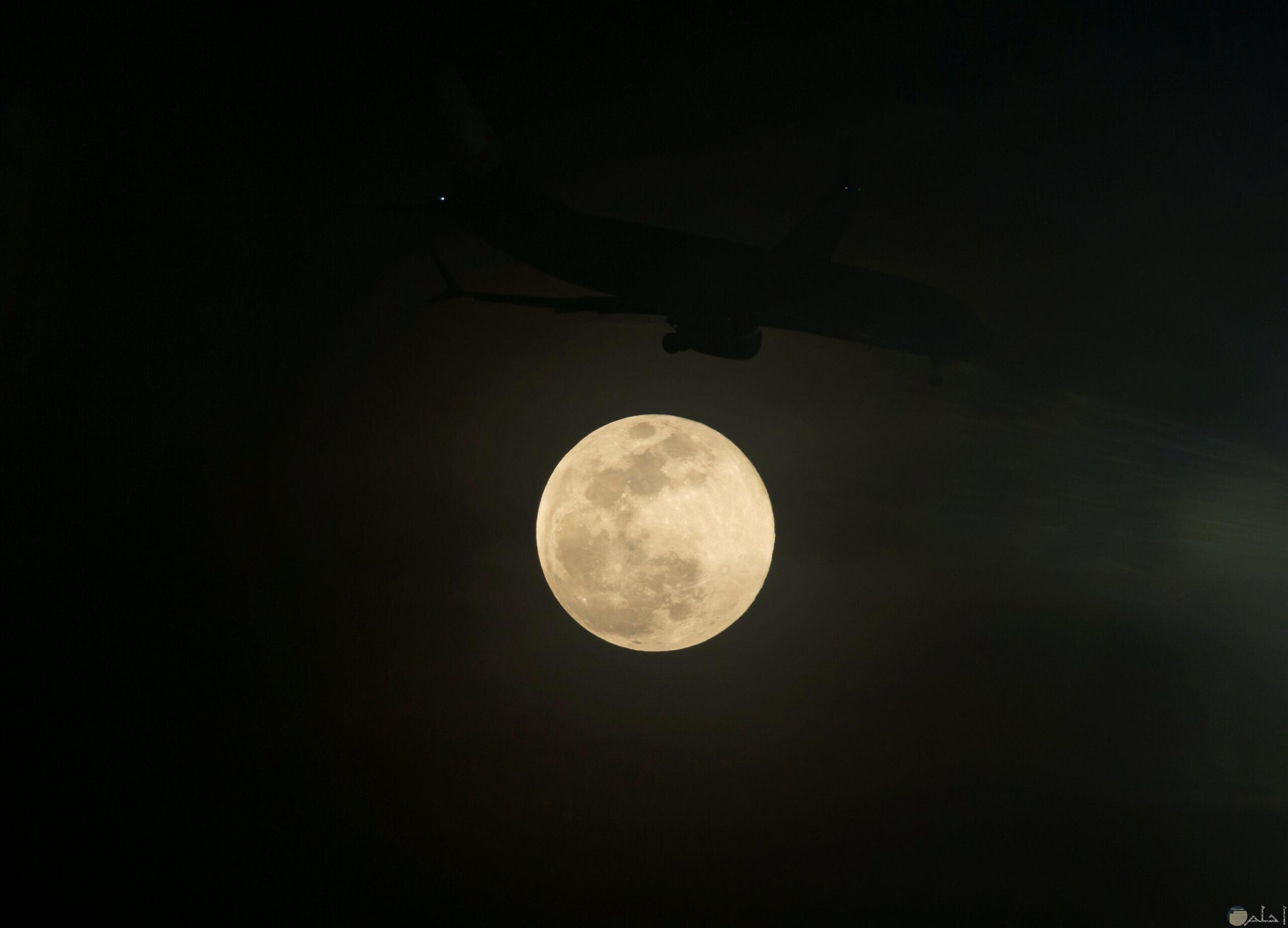 نور القمر يشع بين السحاب ليلاً.